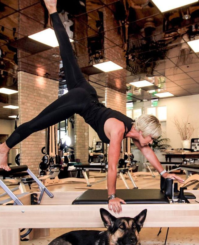 woman using Pilates reformer at BOARD30 Park City