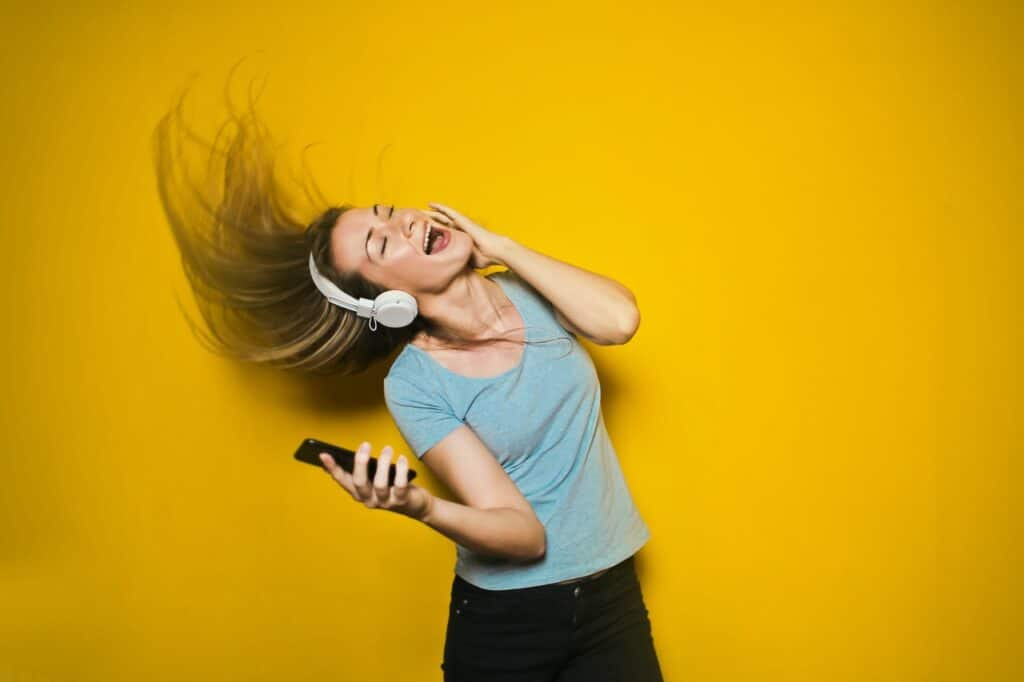 woman dancing with white headphones on yellow background to workout playlist
