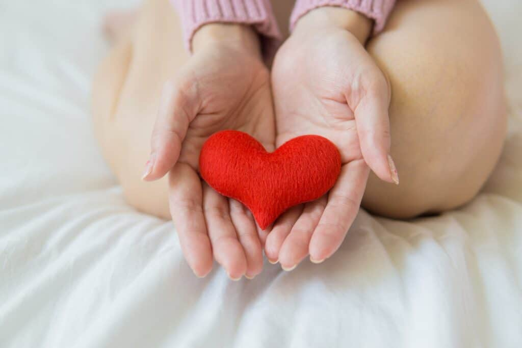 person kneeling on white bed holding red cloth heart in open hands to promote healthy snacking and heart month