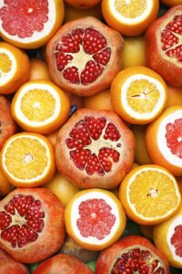 a mix of oranges and pomegranates cut in half so their seeds show