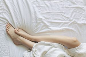 woman's feet laying in bed with white sheets and bedding
