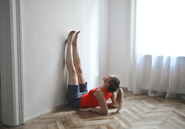woman in workout gear resting up on her elbows with her legs straight up on the wall