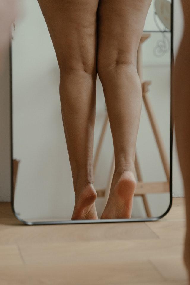 woman's legs standing in mirror